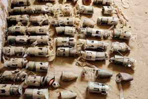 These are the individual sub-munitions from the BL-755 aircraft bomb.   From the series of poictures, it appears that there was a single weapon that malfunctioned, landing on the ground with dispersing all (or possibly any) of its cargo of 147 bomblets. Around 11-15 bomblets remained in the crushed remains of the bomb; a further 68-72 are laid out in the tiled room.  Thus the total recovered is roughly between 79 and 87.   This is more than half the original number packed in the bomb.The cluster bomb was most likely dropped by Saudi Arabia-led coalition forces. Out of the coalition members, UAE and Saudi Arabia are known to possess this type of cluster bombs in their stockpiles. Picture taken at YEMAC (local demining organisation) storage center in Hayran, Hajjah.