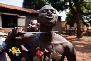 An Anti-Balaka fighter, member of a militia opposed to the Seleka rebel group, puts a knife to his throat showing what he would do to any Seleka, on the outskirts of the Boy-Rabe neighborhood in Bangui on December 14, 2013. France raised alarm on December 13 over worsening violence in the Central African Republic, as UN chief Ban Ki-moon urged warring Christians and Muslims to stop the bloodshed that has left more than 600 dead in the past week. AFP PHOTO IVAN LIEMAN (Photo credit should read Ivan Lieman/AFP/Getty Images)